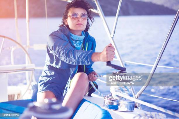 Young woman sailor winding rope on sailing winch