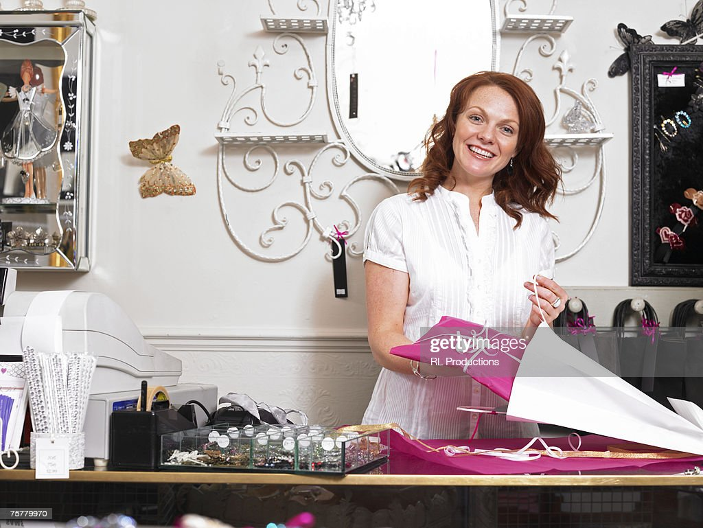 Young woman sales clerk in gift shop, standing behind checkout counter, holding present, smiling : Stock Photo