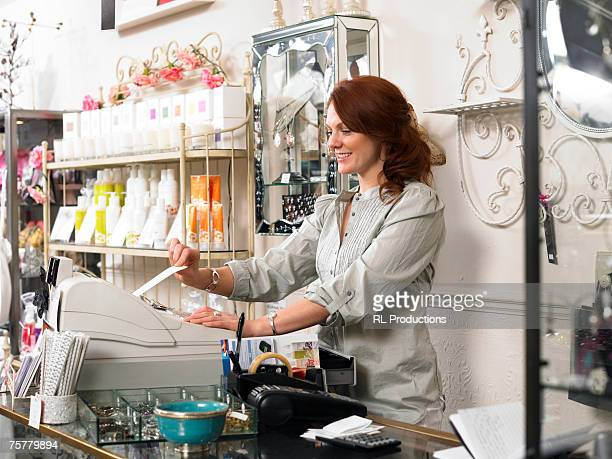young woman, sales clerk in gift shop, using cash register, smiling, side view - ギフトショップ ストックフォトと画像