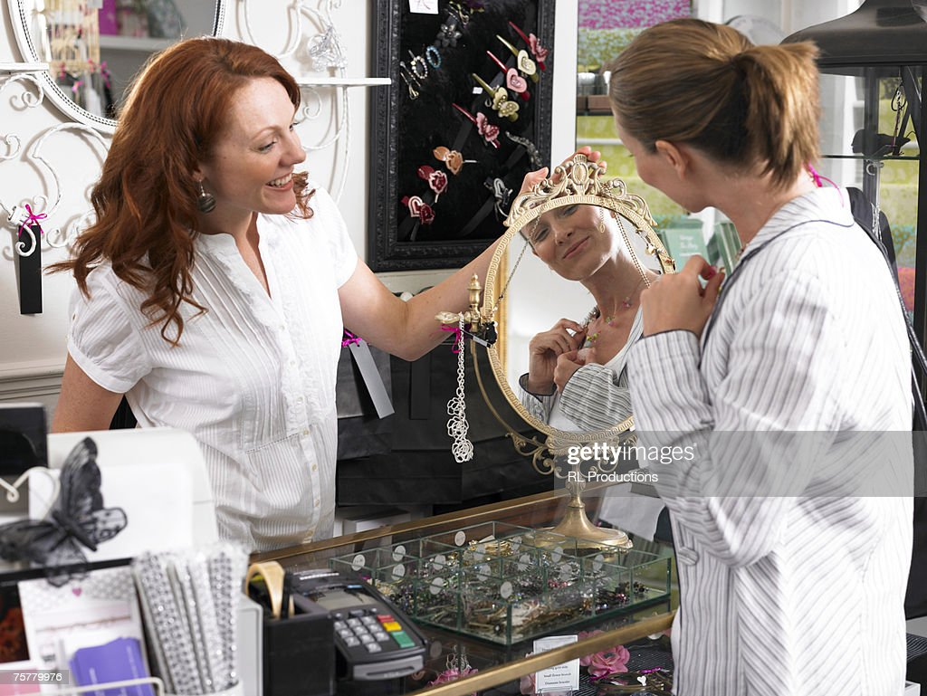 Young Woman Sales Clerk In Shop Holding Mirror Serving ...