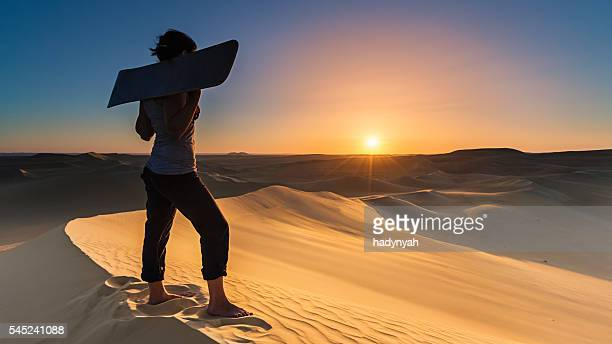 Young woman sandboarding in The Sahara Desert during sunset, Africa