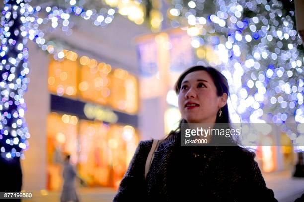 若い女性のクリスマスの照明を通り decolatd で研磨