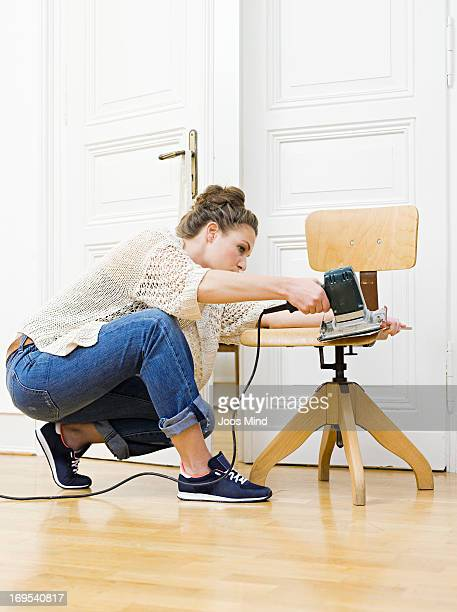 Young woman sanding chair