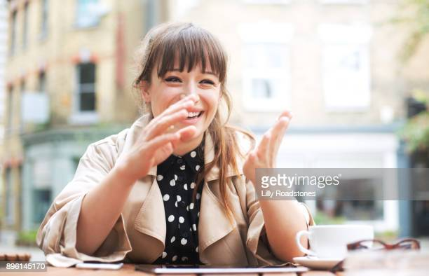Young woman sat at cafe table laughing