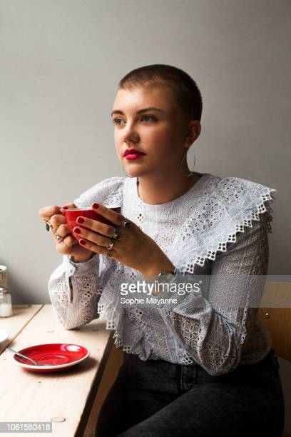 A young woman sat drinking in a coffee shop
