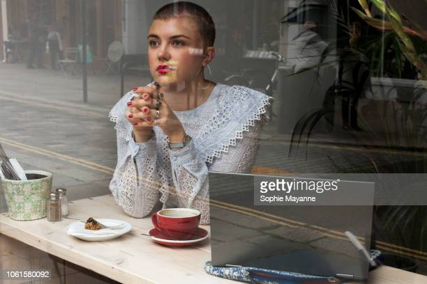 A young woman sat in a coffee shop looking out of the window