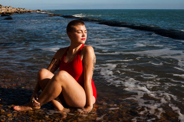 A young woman sat in the sea looking over her shoulder