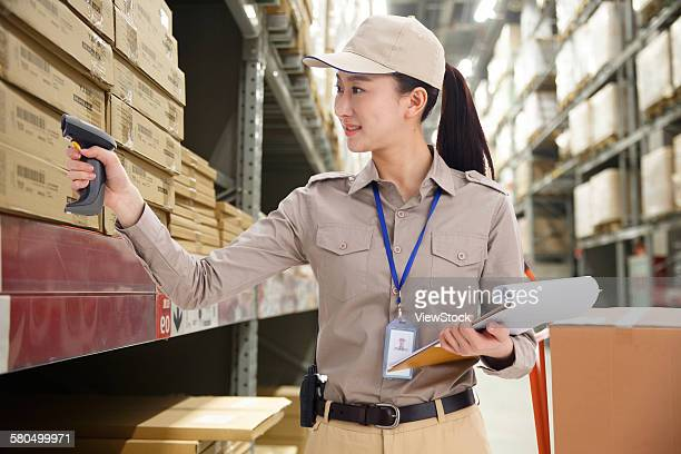 Young woman scanning boxes with bar code reader