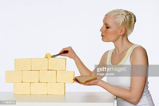 Young woman scraping butter
