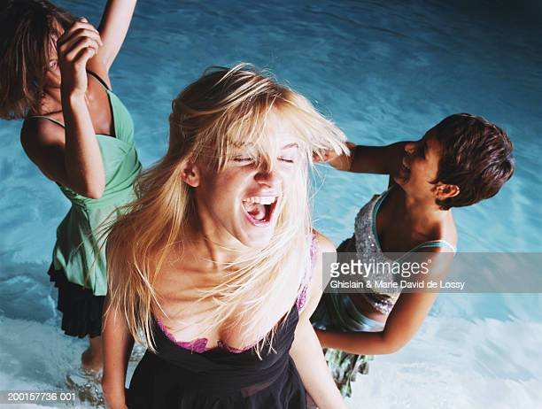 Young woman screaming by two women in pool, elevated view