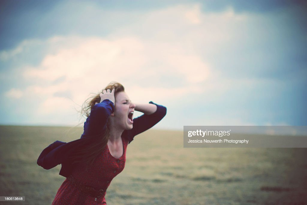 Young woman screaming in windy, cloudy field : Stock Photo