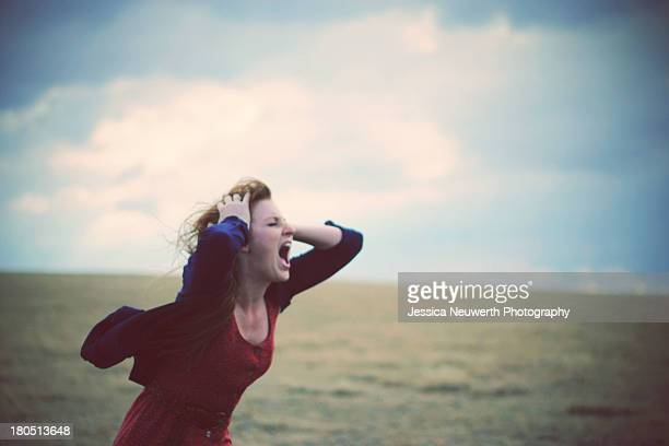 Young woman screaming in windy, cloudy field