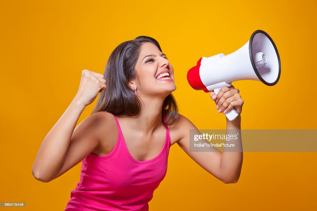 Young woman screaming into a megaphone : Stock Photo