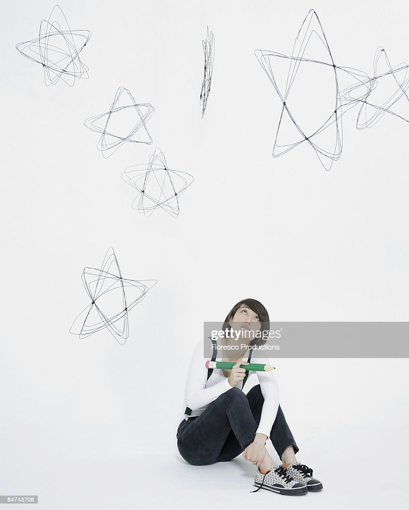Young woman scribbling stars on wall : Foto de stock