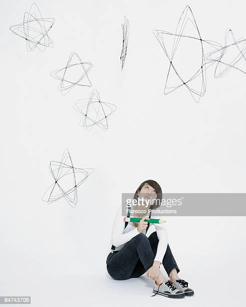 Young woman scribbling stars on wall