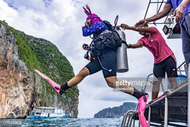 young woman scuba diver in fancy dress diving into sea - só adultos imagens e fotografias de stock