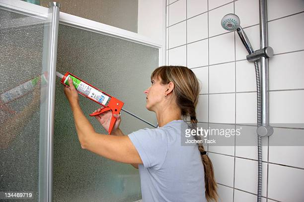 Young woman sealing joints with a plastic composition and the help of a sealant gun in a bathroom
