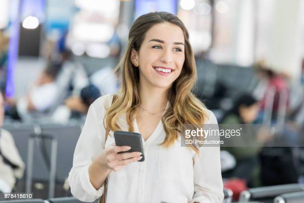 Young woman searches for travel companion in airport terminal