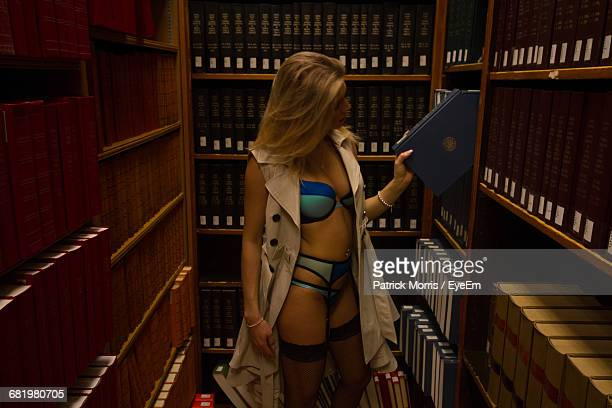 Young Woman Searching Book In Library