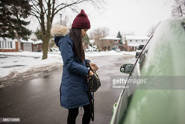 Young woman searching for car keys in her bag