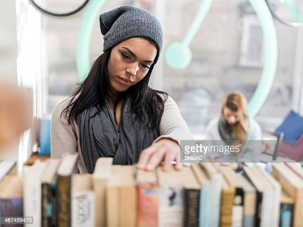 Young woman searching for the right book in a library.