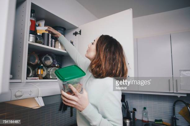 young woman searching in cabinet at kitchen - domestic kitchen stock pictures, royalty-free photos & images