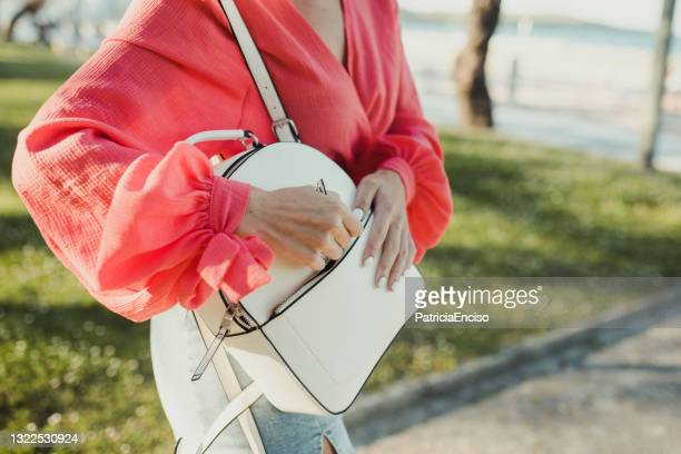 young woman searching in her purse - pink purse stock pictures, royalty-free photos & images