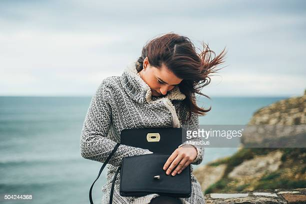 young woman searching in her purse - clutch bag stock pictures, royalty-free photos & images