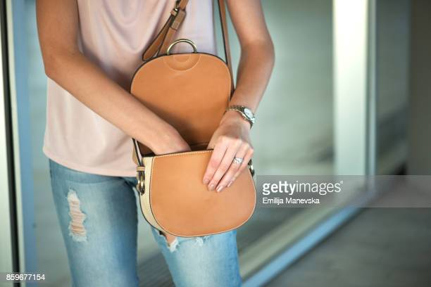 young woman searching in her purse - borsetta da sera foto e immagini stock
