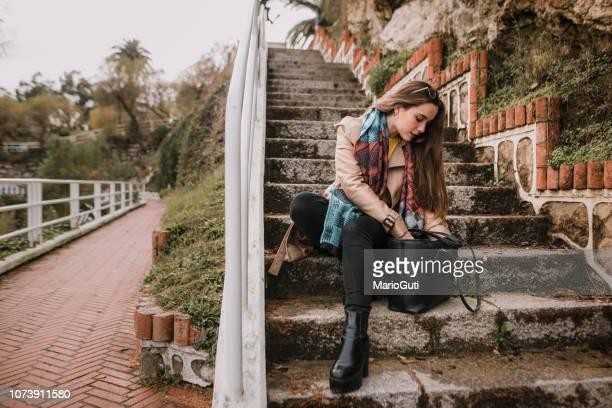 jonge vrouw zoeken op haar tas - handtas stockfoto's en -beelden