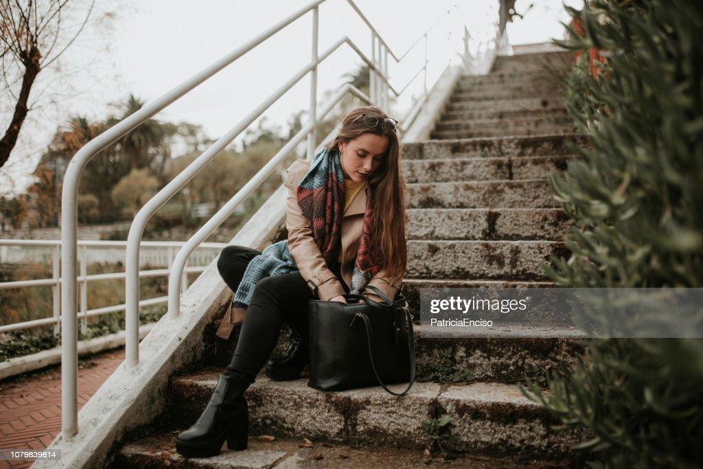 Young woman searching on her bag : Stock Photo