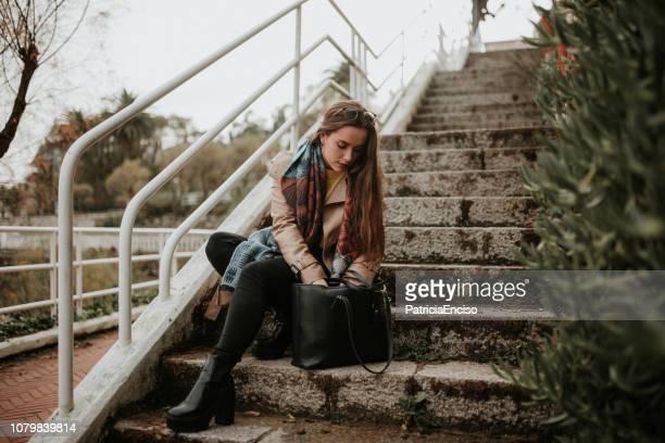 junge frau auf der suche auf ihre tasche - handtasche stock-fotos und bilder
