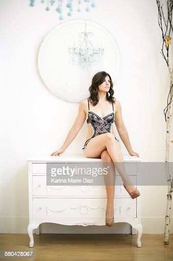 Young Woman Seated On White Armoire In Lingerie High-Res ...