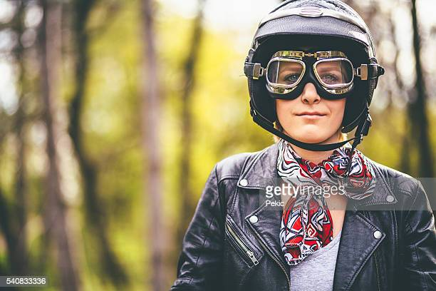 Young woman seating on a motorcycle wearing motorcycling clothes