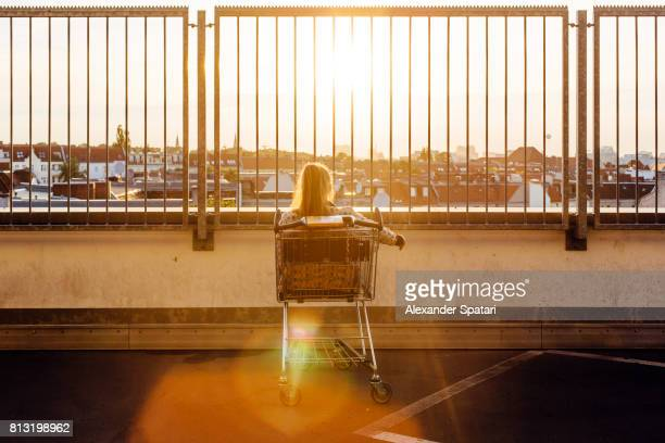 Young woman seen from behind sitting in a shopping cart and looking at sunset through the fence