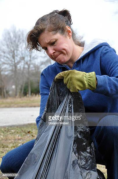Young woman seen outdoors filling a trash bag with litter in perpetrating for Earth Day