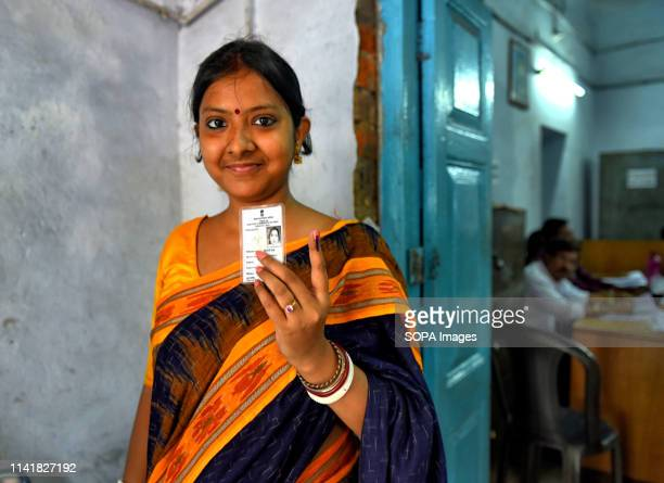 Young woman seen showing her ink marked finger after casting the vote at a polling station during the 5th Phase of General Elections of India.