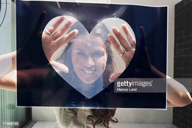 Young woman seen through heart shaped graphic.