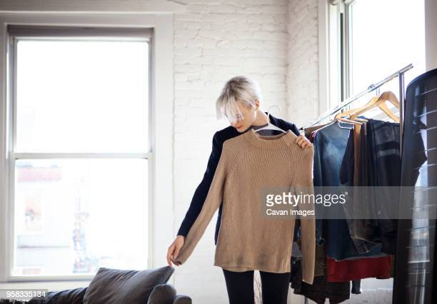 young woman selecting clothes at home - rack stock pictures, royalty-free photos & images
