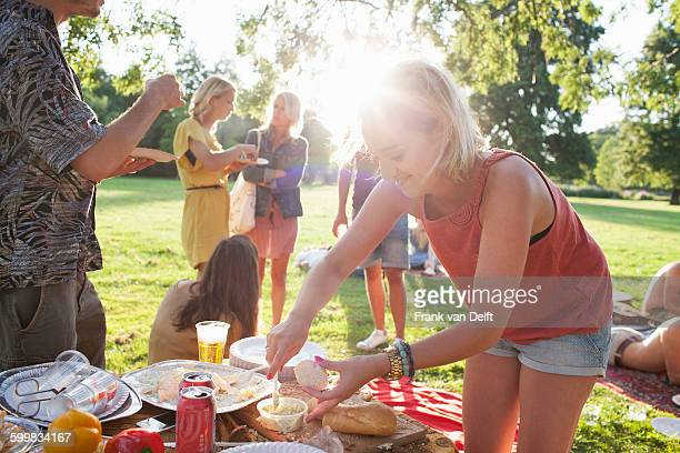Young woman selecting food at group party picnic in park