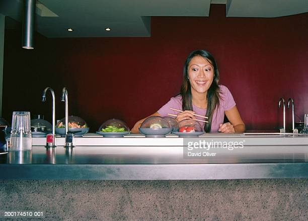 young woman selecting food at sushi bar - sushi restaurant stock photos and pictures