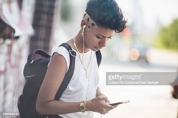 Young woman selecting music on smartphone