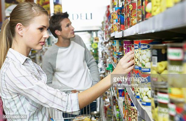 Young woman selecting product from supermarket shelf, side view