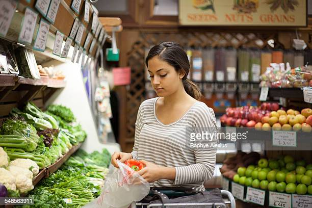 young woman selecting red pepper at health food store - produce aisle stock photos and pictures