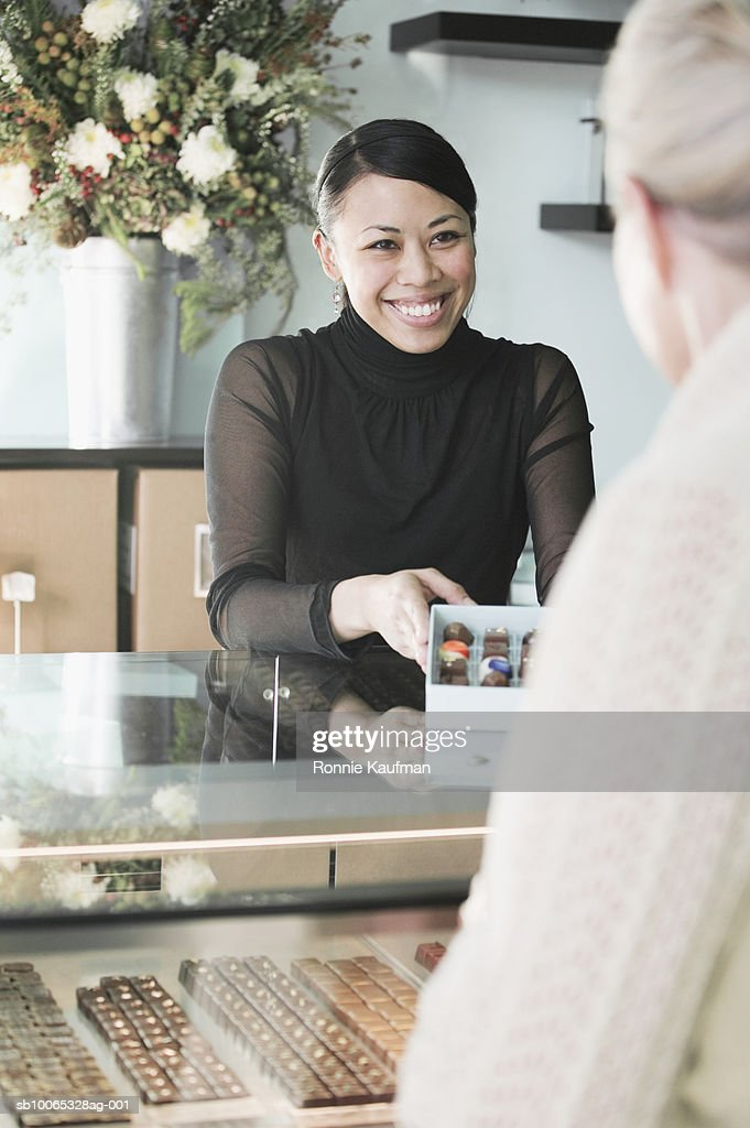 Young woman selling chocolates to senior woman in chocolate shop : Foto stock