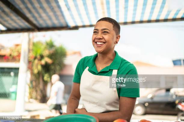young woman selling fruits to a customer in a street market - street market stock pictures, royalty-free photos & images