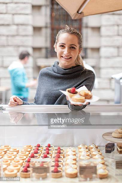 Young woman selling pastries at market