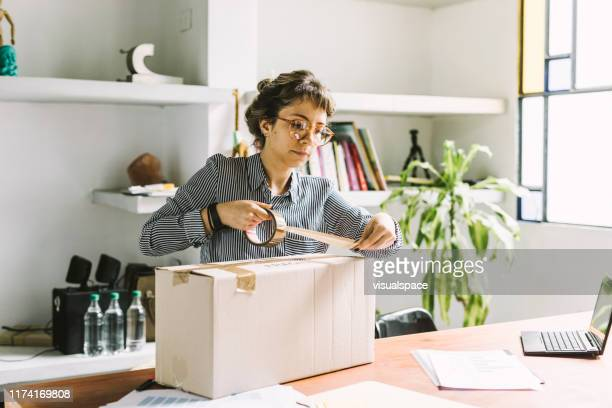 young woman sending a package - sending stock pictures, royalty-free photos & images
