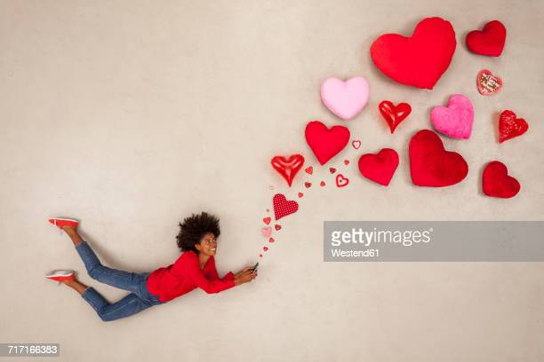 Young woman sending hearts from her phone
