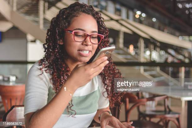 young woman sending voice message or using smartphone voice recognition - speech recognition stock pictures, royalty-free photos & images